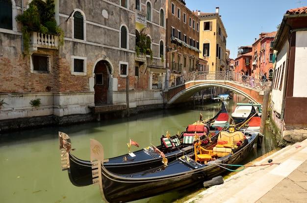 Gondole sur le canal grande. gondoles amarrées sur canal. service de gondole les touristes voyagent autour de venise en italie