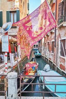 Gondole et le drapeau de la ville sur le canal à venise, en italie. journée ensoleillée.