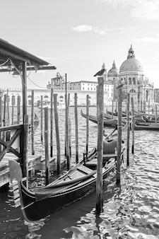 Gondoles amarrées et église santa maria della salute à venise, italie. noir et blanc