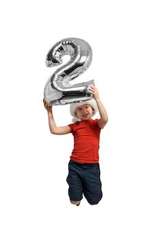 Gonflable en argent numéro 2 dans les mains d'un garçon sautant dans un chapeau rouge,