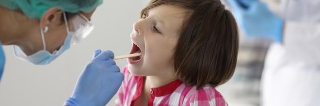 La gorge de la petite fille est examinée sur rendez-vous chez le médecin.