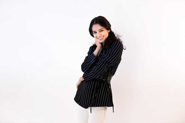 Gorgeours jeune femme brune européenne vêtue d'une veste noire et d'un pantalon blanc, regardant la caméra