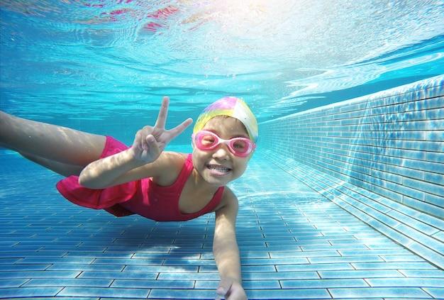 Gosse asiatique heureux nager sous l'eau en été
