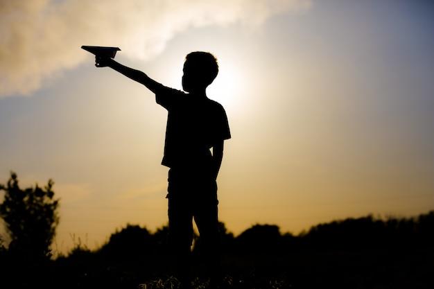 Gosse, jouer, à, avion papier, dans, les, coucher soleil