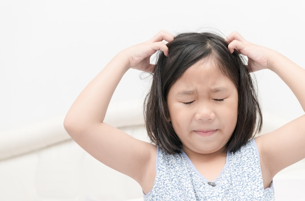 Gosse avec taches de rousseur gratter ses cheveux pour les poux de tête ou des allergies, concept de soins de santé