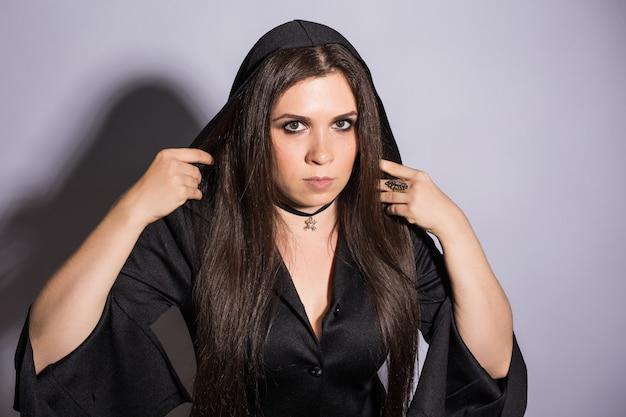Gothique jeune femme en costume d'halloween de sorcière avec une citrouille sculptée.
