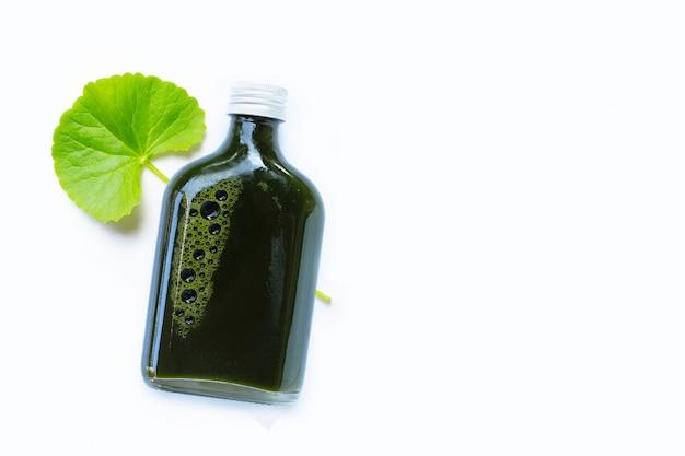 Gotu kola laisse du jus pour la santé sur une surface blanche
