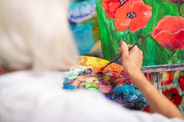 Gouache colorée. gros plan d'une femme talentueuse mélange de gouache colorée tout en peignant des coquelicots