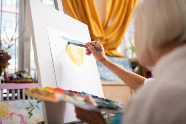 Gouache colorée. gros plan d'une femme talentueuse peinture avec gouache colorée en atelier
