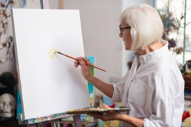 Avec gouache jaune. femme talentueuse à la retraite aux cheveux blonds, peinture à la gouache jaune