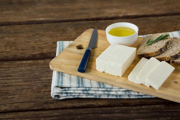 Gouda, tranches de pain brun et jus de citron vert avec un couteau sur une planche à découper