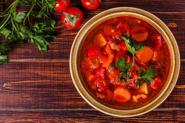Goulache ou ragoût dans un bol servi avec du persil sur fond de bois.