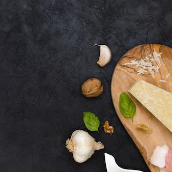 Gousse d'ail; noix entière; basilic; club de fromage et ail sur fond texturé noir
