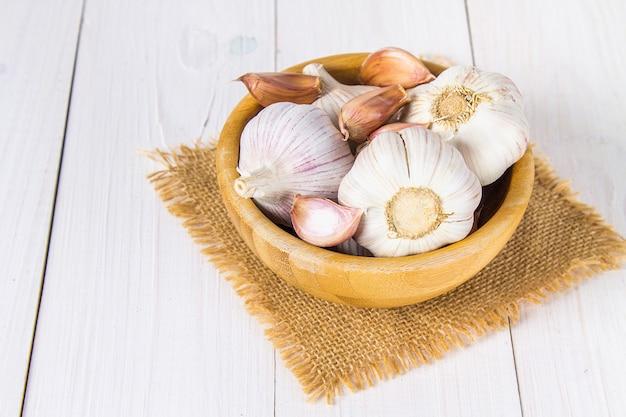 Gousses d'ail et bulbe d'ail dans un bol sur une table en bois blanche.
