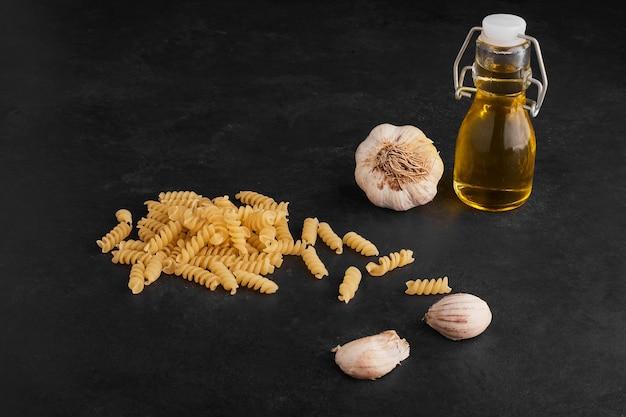 Gousses d'ail isolées sur une surface noire avec des pâtes et de l'huile d'olive.