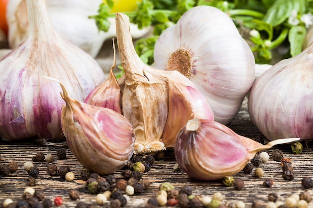 Gousses d'ail mûr sur la table de la cuisine pendant la cuisson d'un plat avec de l'ail, de l'ail tranché sur une planche à découper qui est ajouté à la nourriture pour donner un goût agréable