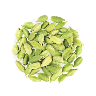 Gousses de cardamome isolés sur blanc. graines de cardamone verte. chemin de détourage. vue de dessus.