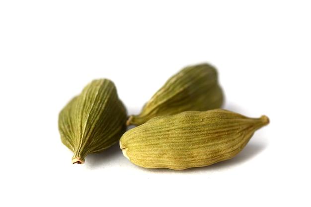 Gousses de cardamome sur surface blanche