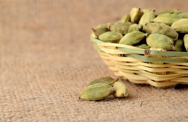 Gousses de cardamome verte dans un panier en bambou sur toile de sac