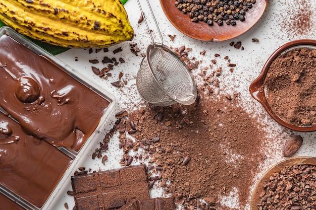 Gousses de fèves de cacao, morceaux de barres de chocolat, poudre de cacao
