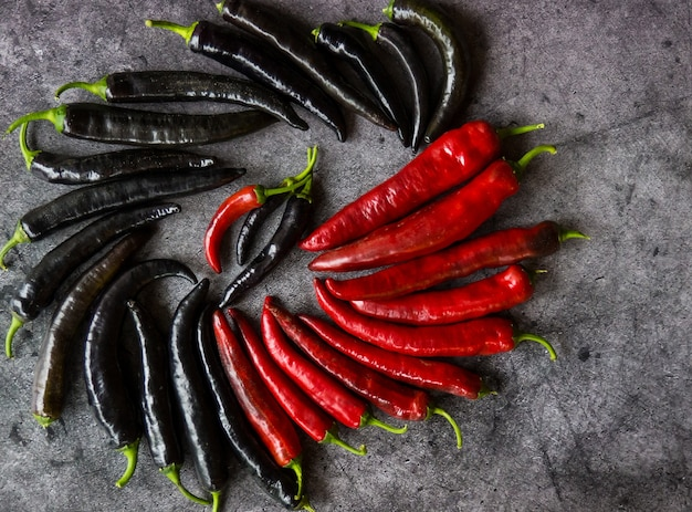Gousses de piment de poivre rouge et noir sur fond de béton foncé