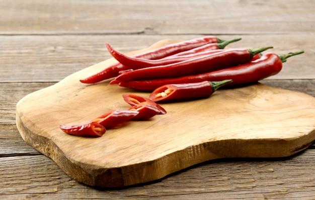 Gousses de piment rouge paprika sur une planche de bois.