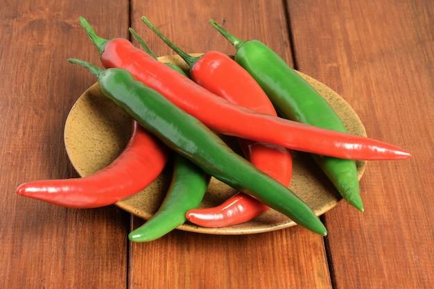 Des gousses de piments rouges et verts sont éparpillées sur une plaque en céramique marron sur une table en bois marron