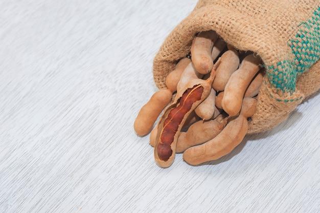 Gousses de tamarin pour soupe d'assaisonnement aux crevettes tom yum sur pieux dans un sac de jute biologique sur un fond en bois blanc, flat lay