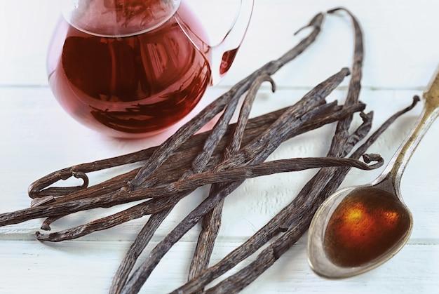 Gousses de vanille sèches et cuillère avec extrait aromatique sur table