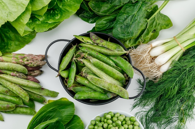 Gousses vertes aux petits pois, épinards, oseille, aneth, laitue, asperges, oignons verts dans une casserole sur mur blanc, vue de dessus.