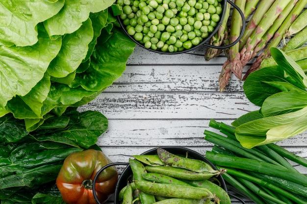 Gousses vertes, pois dans des casseroles avec asperges, tomate, oseille, épinards, laitue, oignon vert vue de dessus sur un mur en bois
