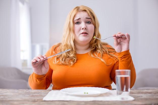 Goût horrible. insatisfait femme forte assise à la table et manger des pois