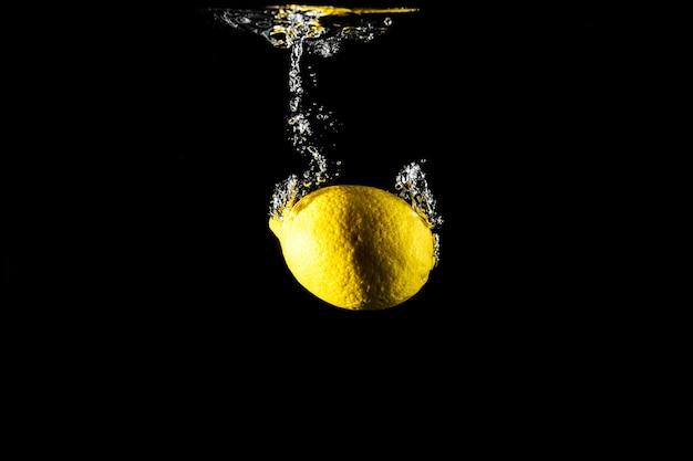 Goutte de citron dans l'eau fond noir