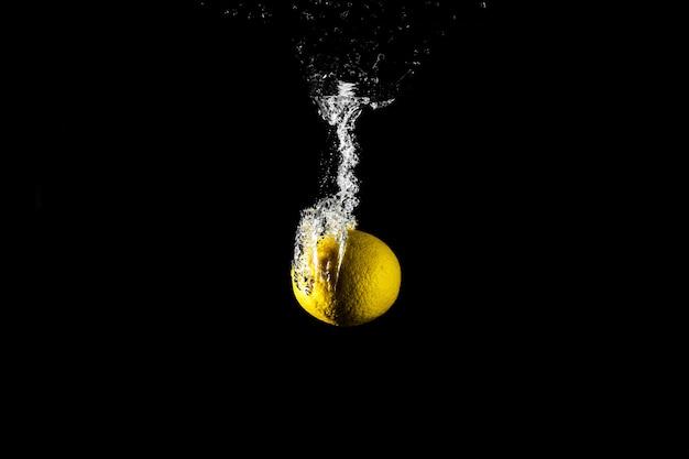 Goutte de citron dans l'eau noire