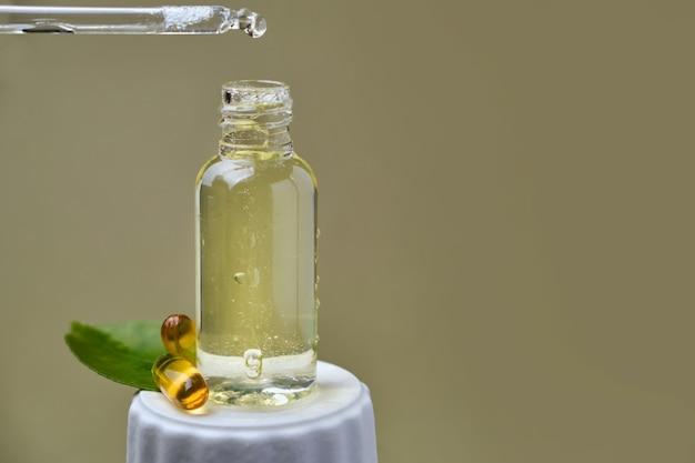 Une goutte d'huile d'agrumes en gros plan s'égoutte d'une pipette dans une bouteille sur une surface verte avec de belles feuilles juteuses de mandarine