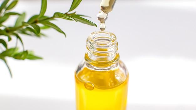 Une goutte d'huile essentielle ou biologique jaune dans une pipette en verre au-dessus du flacon