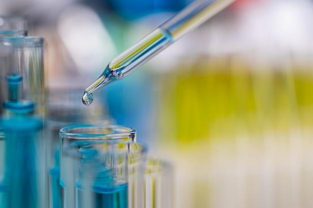 Goutte de liquide bleu du compte-gouttes tombant dans le tube à essai en laboratoire avec un arrière-plan flou de couleur vive.