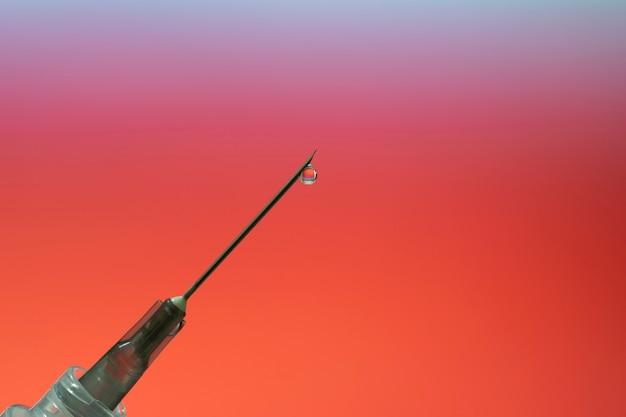 Goutte de médicament sur l'extrémité de l'aiguille de la seringue. fond de pourriture rouge.