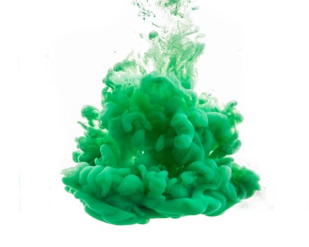 Goutte de peinture verte tombant dans l'eau