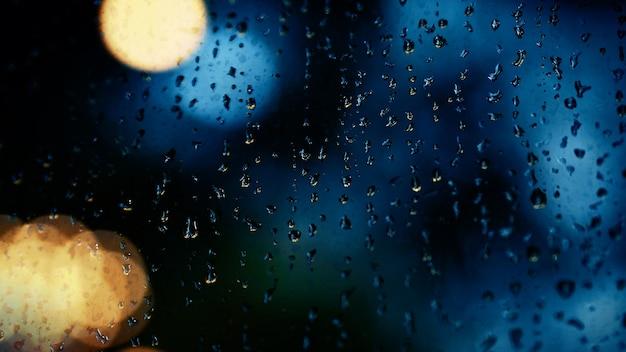 Goutte De Pluie Sur La Fenêtre La Nuit. Fenêtre Du Salon En Copropriété Ou En Appartement La Nuit De La Saison Des Pluies à Bangkok En Thaïlande. La Fenêtre Extérieure Est Un Bokeh Flou De La Pluie De La Lumière De La Ville Et De L'arbre Et Du Ciel Naturels. Photo Premium