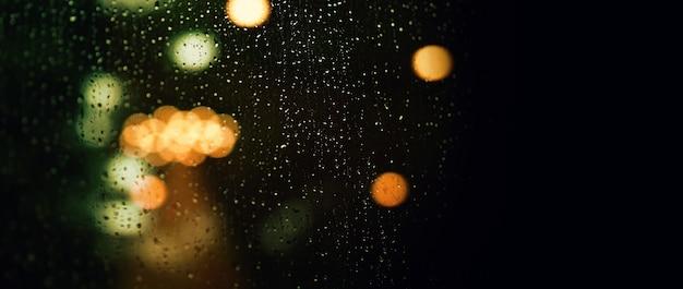 Goutte de pluie sur la fenêtre la nuit. fenêtre du salon en copropriété ou en appartement la nuit de la saison des pluies à bangkok en thaïlande. la fenêtre extérieure est un bokeh flou de la pluie de la lumière de la ville et de l'arbre et du ciel naturels.