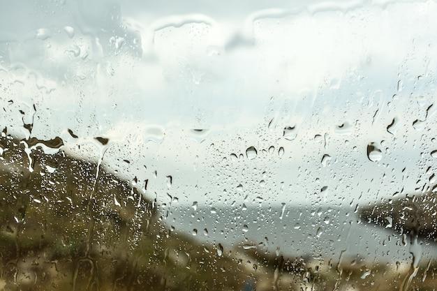 Goutte de pluie floue sur le fond de verre de la voiture, gouttes d'eau à la fenêtre de la voiture
