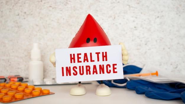 Une goutte de sang jouet contient une carte en papier blanc avec l'inscription assurance maladie. concept médical.