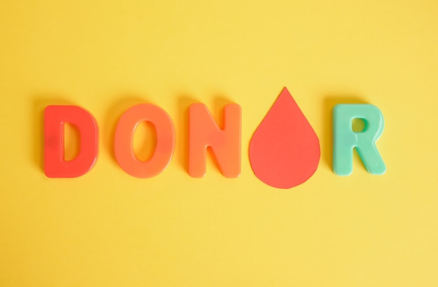Une goutte de sang de papier et le donneur d'inscription de lettres en plastique sur fond jaune