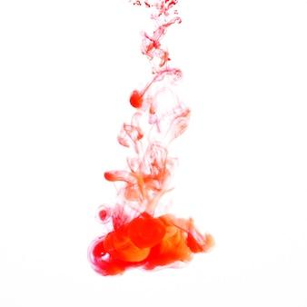 Gouttelette d'encre légère orange qui coule dans l'eau