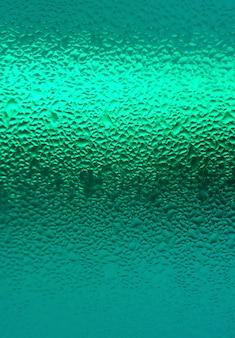Gouttelettes d'eau sur une bouteille de couleur bleu turquoise
