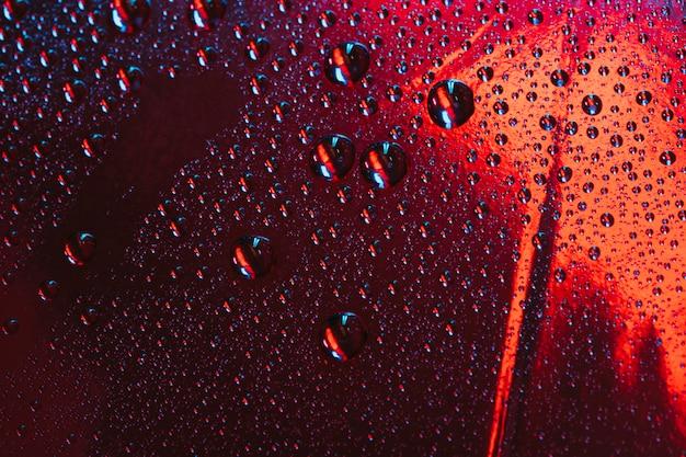 Gouttelettes d'eau sur le verre réfléchissant rouge