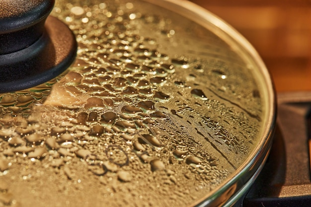 Gouttes sur le couvercle en verre de la poêle à frire préparant le plat au four avec mise au point sélective