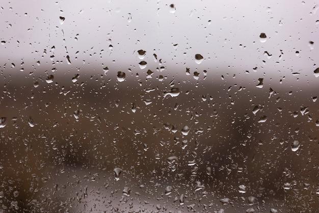 Gouttes d'eau après la pluie dans une vitre sombre