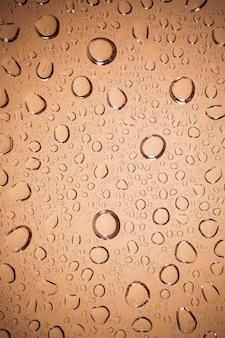 Gouttes d'eau sur fond de verre marron.